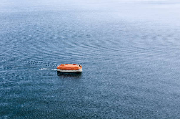 enclosed rigid lifeboat awaiting rescue on sea expanse - livbåt bildbanksfoton och bilder