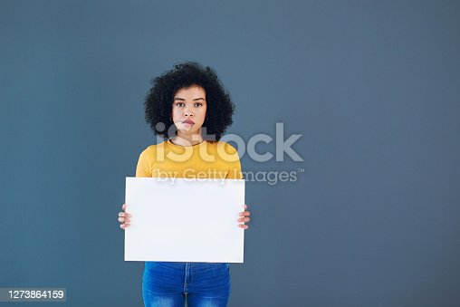 Studio portrait of an attractive young woman holding a placard with the words