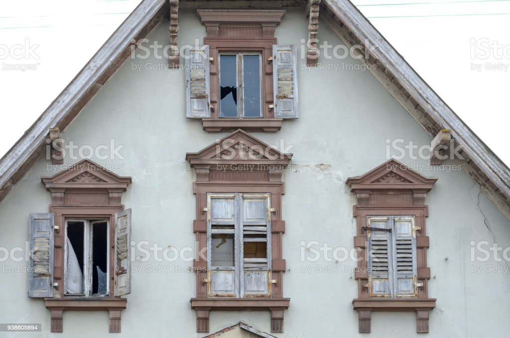 End gable and windows of an old abandoned house stock photo