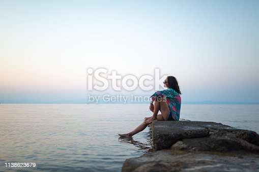 Young woman enjoying by the sea with feet in the water, looking at view, side view