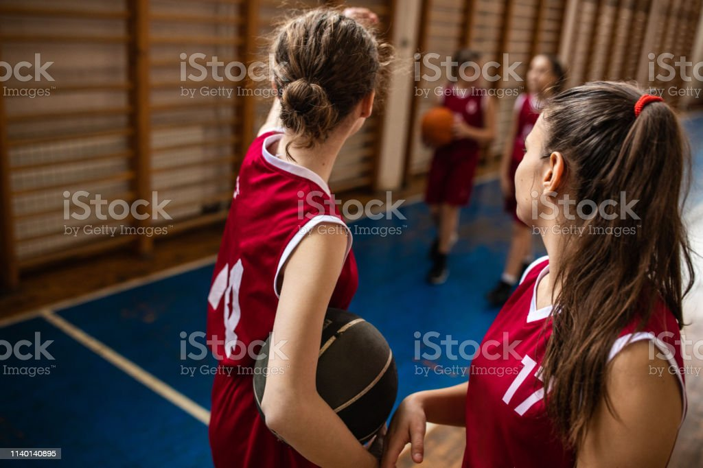 Teenage girls walking and holding basketball ball after training