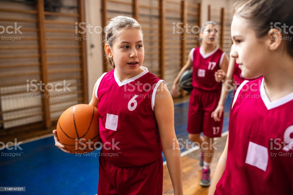 Teenage girls walking and holding basketball ball after training,...