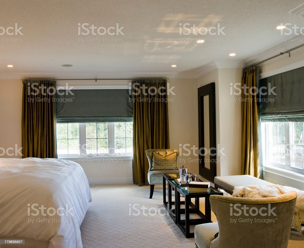End of bed side view of a modern bedroom with large windows  stock photo