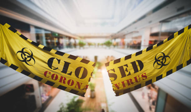 End of coronavirus COVID-19 economic lockdown. Tearing caution tape at shopping mall. stock photo
