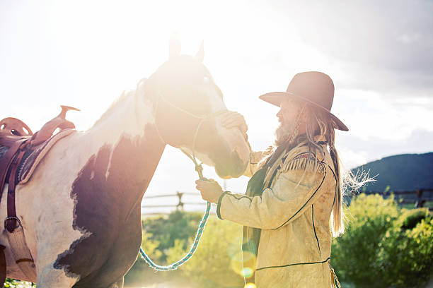 End of Day Moutain Man and Horse Mountain man with pinto horse at the end of a long day. Natural lens flare, added grain and vintage processing. Taken at the Alien Cowboy Stampede. paint horse stock pictures, royalty-free photos & images