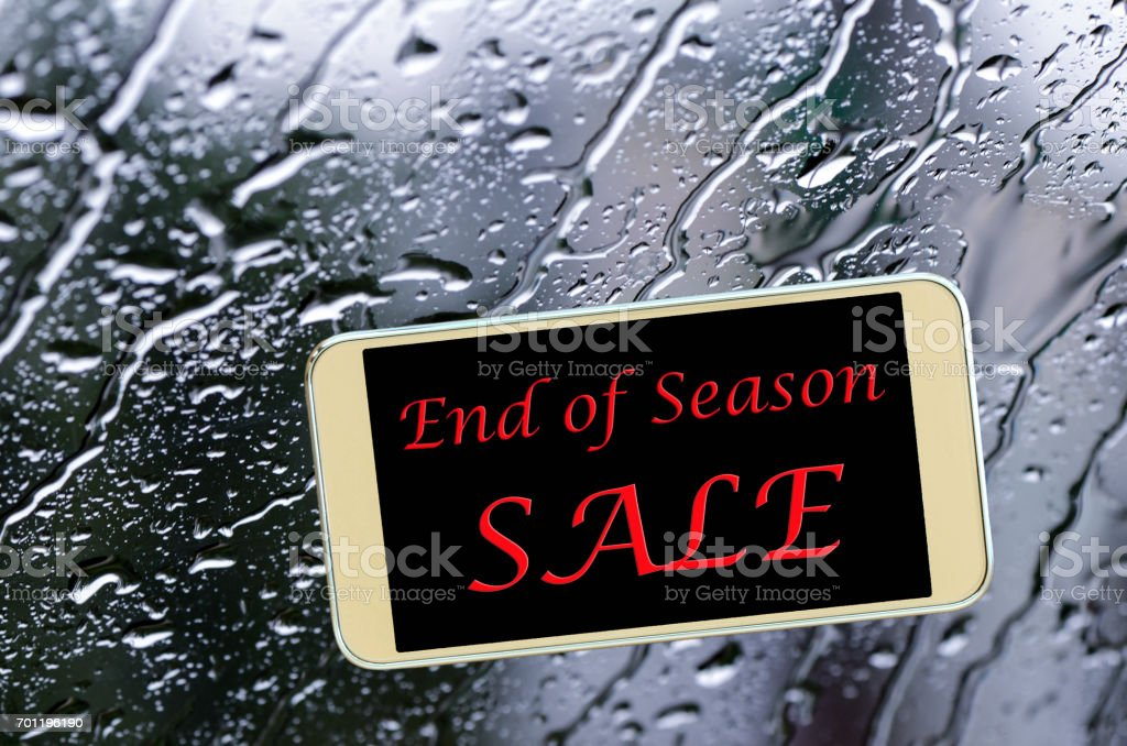 End of season sale sign on glass window with rain drops. stock photo