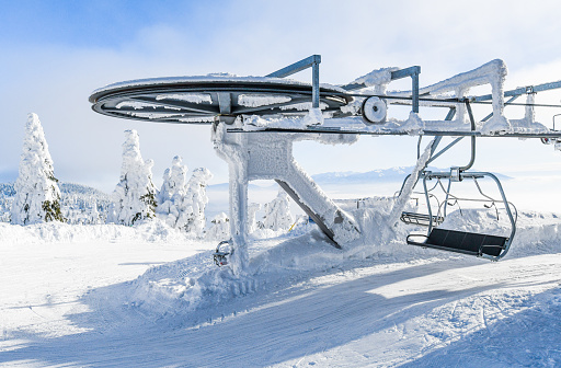 End of ski lifts high in frozen mountains. Winter empty lift seats in winter holiday