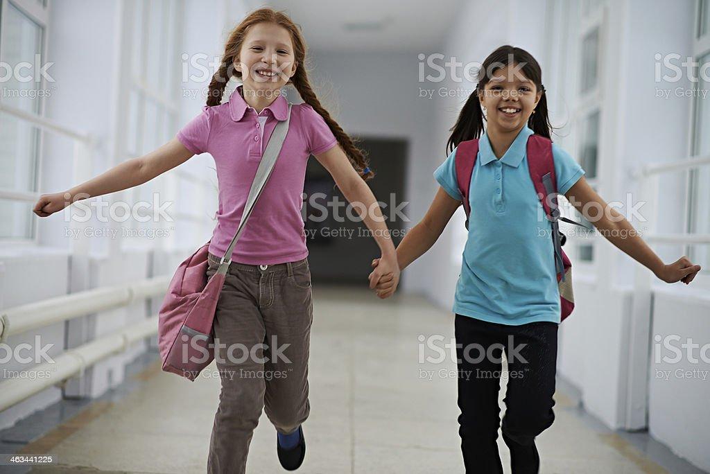 Happy pupils running along school corridor