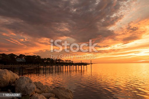 The sun sets over Apalachicola Bay, Florida, overlooking the rocks and a pier on St George Island.