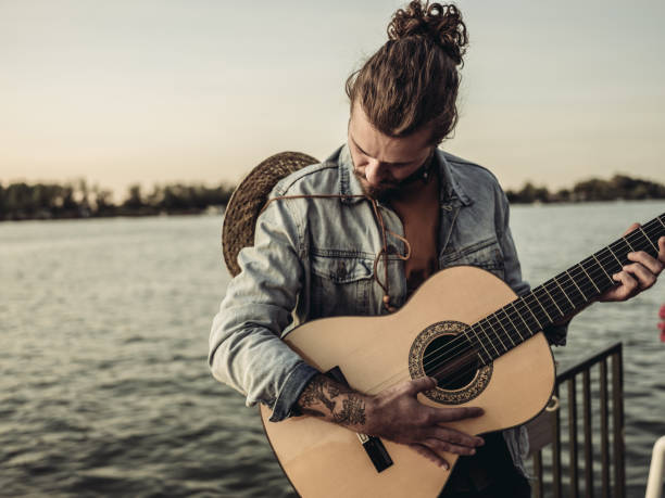 End of the summer Portrait of the young man with guitar looking over river water. End of the summer weekend. man bun stock pictures, royalty-free photos & images