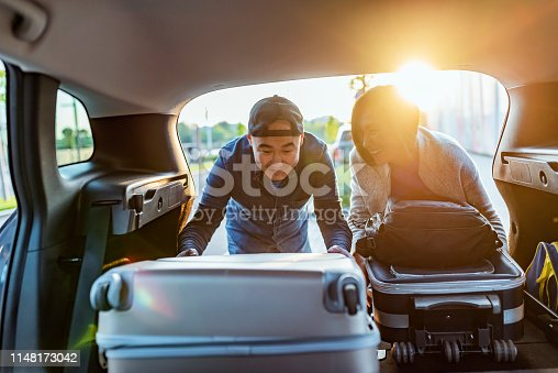 Close-up Of Asian Couple Putting Luggage In A Car Trunk during the day. The young couple helping each other unloading luggage. Portrait of the Asian family putting a suitcase into the car trunk, ready for a holiday together. Happy Asian young man and woman with their suitcase put in the car trunk. preparing for vacation.