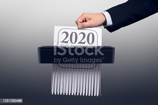 New year 2020 / 2021. Businessman pushes 2020 calendar into a paper shredder. A paper document with 2020 printed on the top is half-shredded.