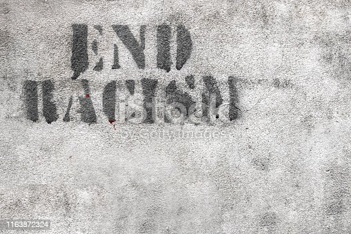 Graffiti on brick wall say - END RACISM. Ideal for concepts and backgrounds.