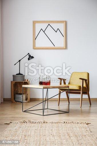 End table with mustard armchair, a lamp on the wooden basket, and a frame with mountains on the wall above