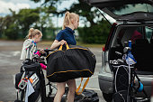Golfing sisters pack away golf equipment into their car ready to finish their day of golf.