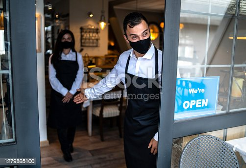Two young adults, male and female waiters, wearing protective face masks, standing at the entrance of a restaurant, welcoming guests, a sign