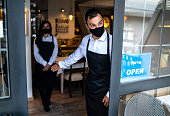 istock Ended lockdown and quarantine in small business. We're open Sign on a restaurant or cafe entrance. 1279865100