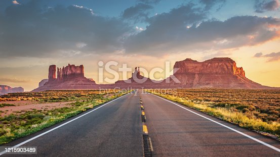Endless highway wide angle Panoramic View under colorful twilight summer sky towards the famous Monument Valley Buttes in Utah. Looking south on U.S. Route - Highway 163 from north of the Arizona–Utah border. Arizona - Utah, USA, North America.