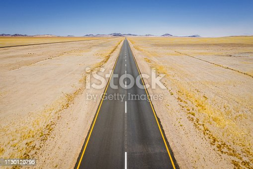 Aerial drone point of view from above along an endless highway to the horizon through the Namibian Prairie - Desert Landscape. Concept Shot. Luderitz - Aus Area, Karas Region, Namibia, Africa.