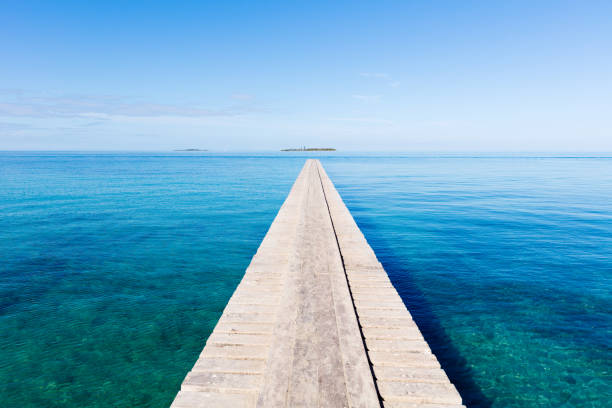 Endless Jetty to the Horizon Noumea New Caledonia Endless wooden jetty over clean turquoise water to the horizon under blue clear summer sky. Noumea Beach, Noumea, New Caledonia, South West Pacific Ocean always stock pictures, royalty-free photos & images