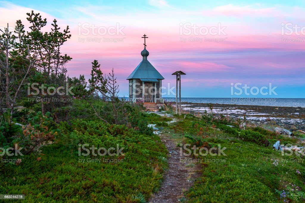 Endless polar day in the Arctic. On the shore of the White sea there is a lonely Christian chapel. Dramatic sky with clouds at night royalty-free 스톡 사진