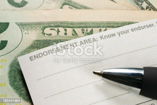 Endorsing the back of a check; Money is present under the check; Pen is slightly blurred.see related: