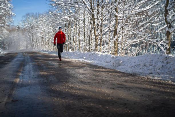 uthållighetsaktiviteter som utbildning på kalla men soliga vintrar dag man jogging alonge road mycket snö på träden och sida av gatan - winter austria train bildbanksfoton och bilder
