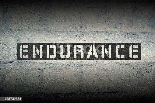 endurance stencil print on the grunge white brick wall