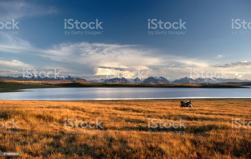 Enduro motorcycle alone traveler on a bank of highland sunset lake on a background of snow ice covered high mountains and glaciers under clouds sky, Plateau Ukok, Altai mountains, Siberia, Russia stock photo