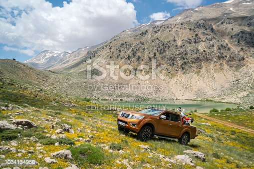 Antalya, Turkey - 1st June, 2017: Nissan Navara Pickup Truck carrying an anduro motorcycle, parked on a hill near yesilgol near Antalya, Turkey.  The newest generation of Navara was debut in 2015 on the market. The Navara is powered by 2,3-litre diesel engine and 190 HP