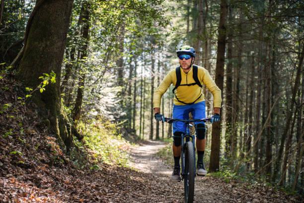 MTB Enduro Mountain Biking in a pristine Forest Man mountain biking through a pristine forest. mountain biking stock pictures, royalty-free photos & images