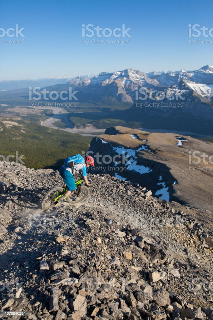 A male mountain bike rider goes down a steep and rocky trail in...