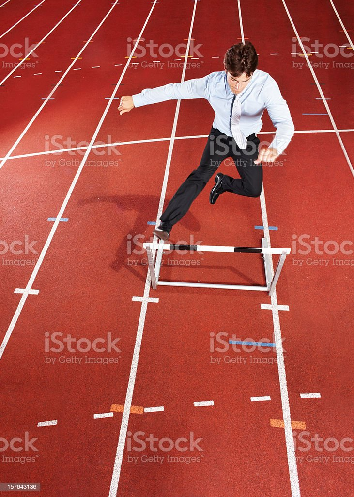 Energetic businessman is jumping over the hurdle royalty-free stock photo
