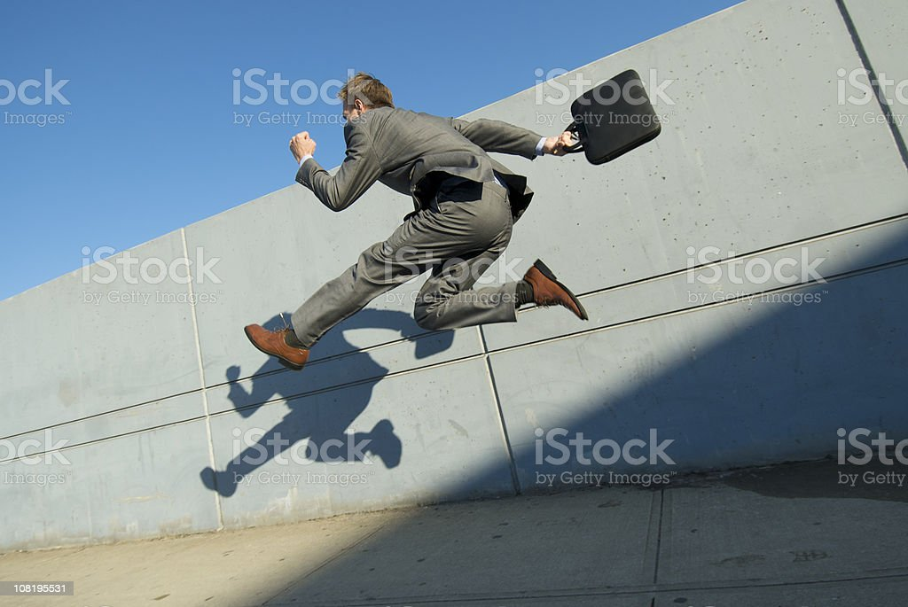 Energetic Businessman Jumping Across City Sidewalk royalty-free stock photo