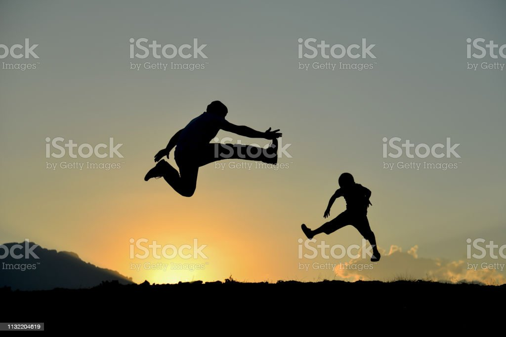 energetic father and son silhouette stock photo