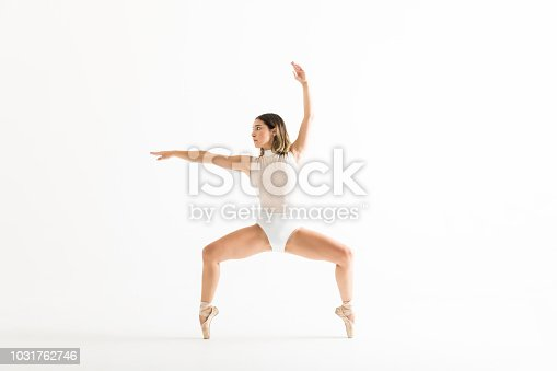 Energetic female dancer performing ballet squat on white background