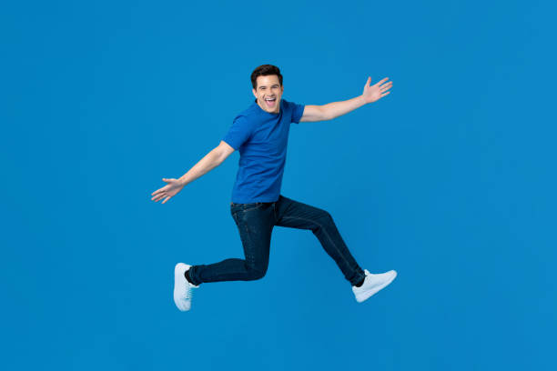 Energetic handsome man jumping and smiling with outstretched hands stock photo