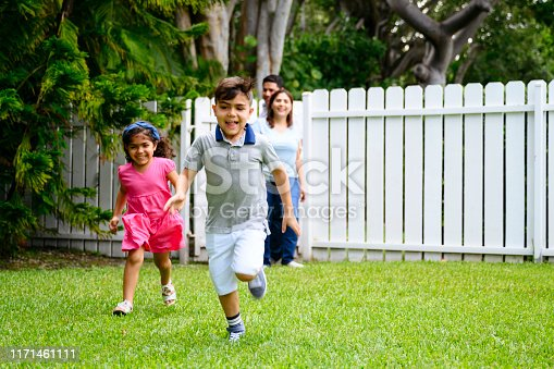 Young Latin American children running across lawn as they return home with mother and father in background.