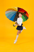 Energetic look. Adorable girl jumping with autumn look on yellow background. Cute little schoolchild having glamour look with colorful umbrella. School look of small child.