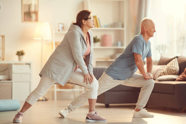 Energetic senior couple in sportswear leaning on knees while stretching legs at home training stock photo
