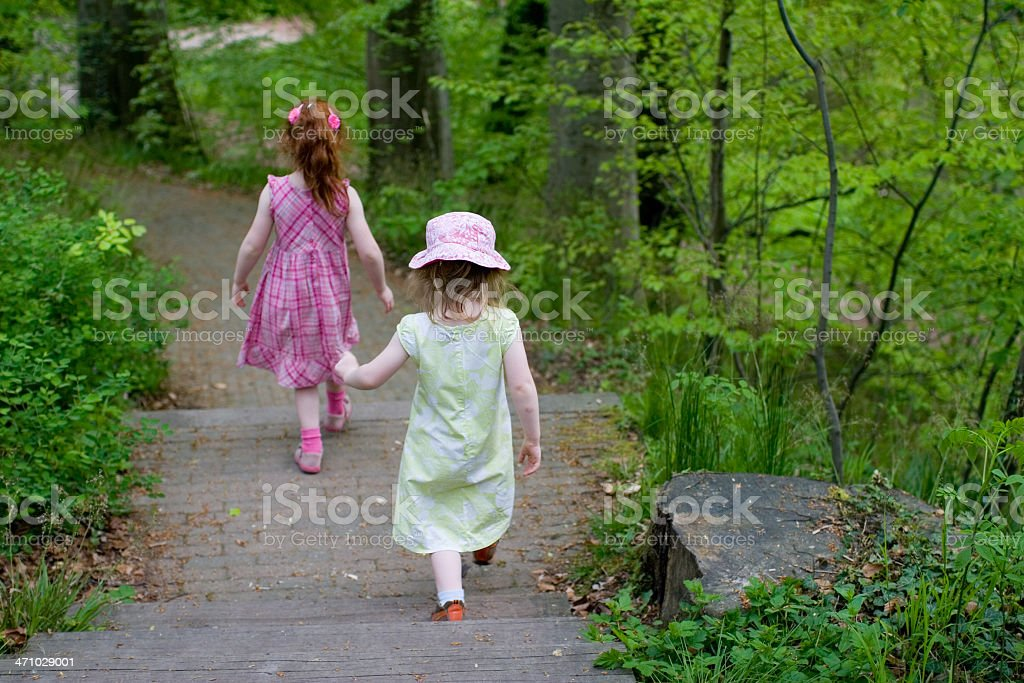 """Energetic walk in the park Two young girls, aged 3 and 5 years, tackling the park with their energetic way of """"walking"""". Active Lifestyle Stock Photo"""