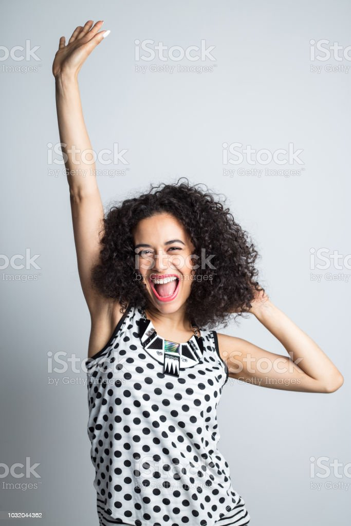 Energetic woman celebrating success Vertical portrait of energetic young woman standing in white background. Mixed race woman with curly hair standing with her hand raised and screaming. 20-24 Years Stock Photo