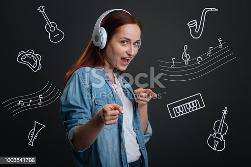 1003539592istockphoto Energetic woman pointing to you while listening to music 1003541766