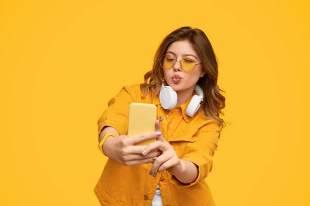Energetic woman with headphones on neck grimacing taking selfie on smartphone stock photo