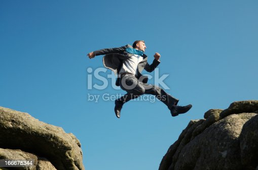 istock Energetic Young Man Businessman Jumping into Blue Sky between Rocks 166678344