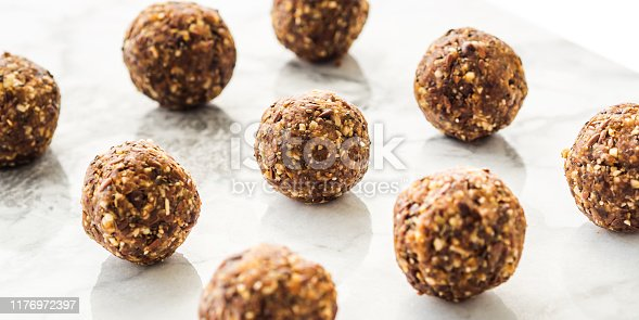 Energy protein balls with healthy ingredients on marble table. Home made with dates, peanut butter, flax and chia seeds, oats, almond and chocolate drops. Food modern pattern on marble table