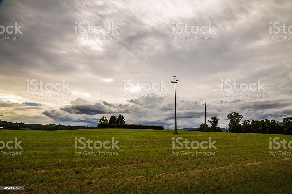 energy cable in the fields of italy stock photo