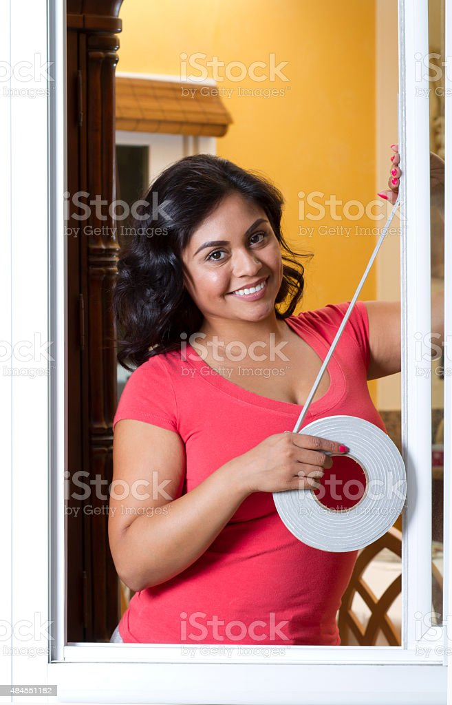 Energy Efficiency Hispanic Woman Applies Weather Stripping Vertical stock photo