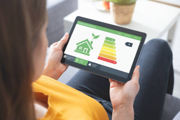 Energy efficiency mobile app on screen, eco house stock photo