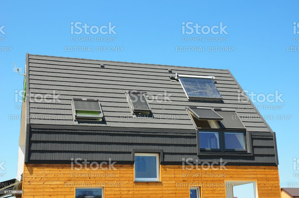 Energy efficiency new passive house building concept. Closeup of solar water panel heating, dormers, solar panels, skylights, ventilation and air conditioning systems installed. stock photo